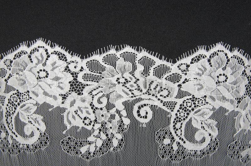 White floral lace on a black. Background royalty free stock photography