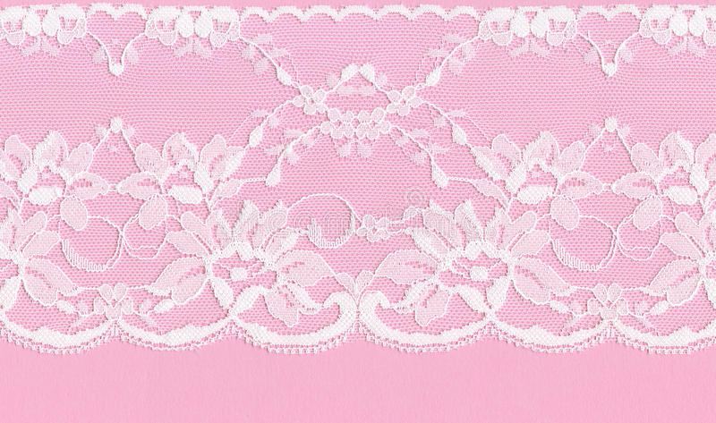 White floral lace on a pink background. Beautiful white floral lace on a pink background royalty free stock photo