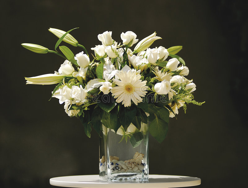 White flower bouquet in vase. A view of a nicely arranged bouquet of white flowers and green leaves in a large vase, sitting on a white table top against a dark stock images