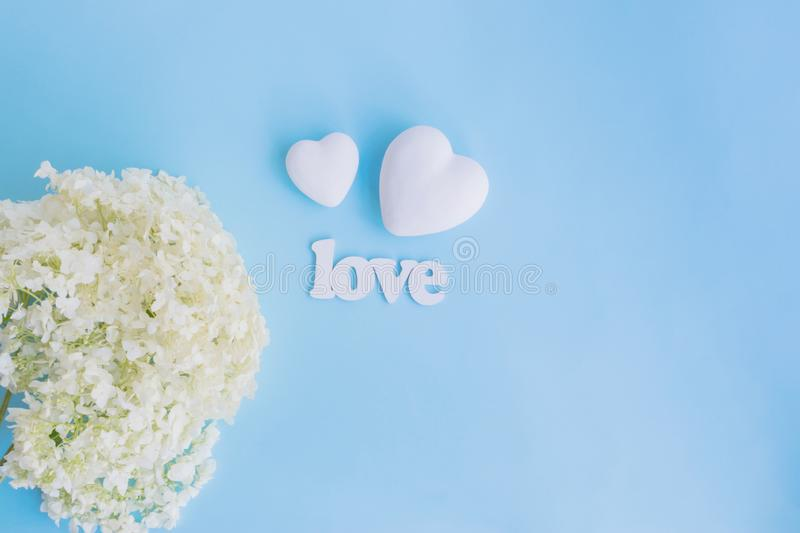 White flower hydrangea and white hearts. On a blue background with letters love royalty free stock photography