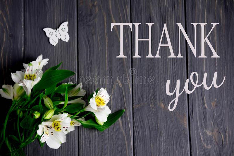 White flowers of Alstroemeria on a dark wooden background with an inscription thank you. Thank you words royalty free stock photography