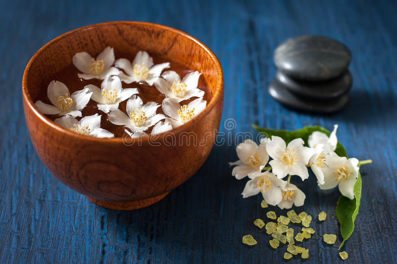 White flowers in a bowl, stones for massage and sea salt. Spa composition. Spa: white flowers in a bowl with water and massage stones and sea salt royalty free stock photography
