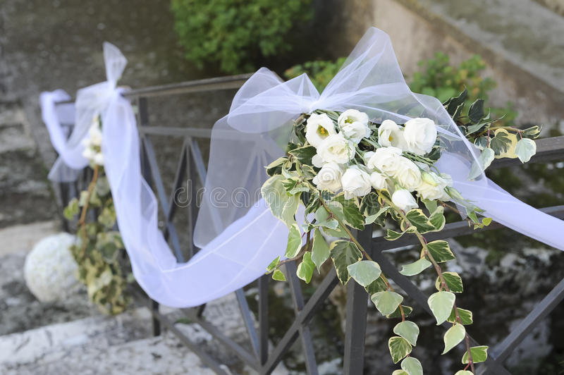 White flowers and bridal veil resting on an iron railing stock image