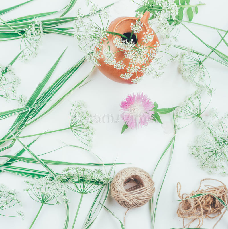 White flowers in a clay pitcher, flower cornflower, a rope and decorative grass of the falaris on a table royalty free stock photography