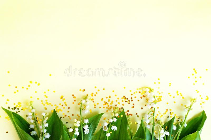 White flowers of a lily of the valley on a warm yellow background. stock photo
