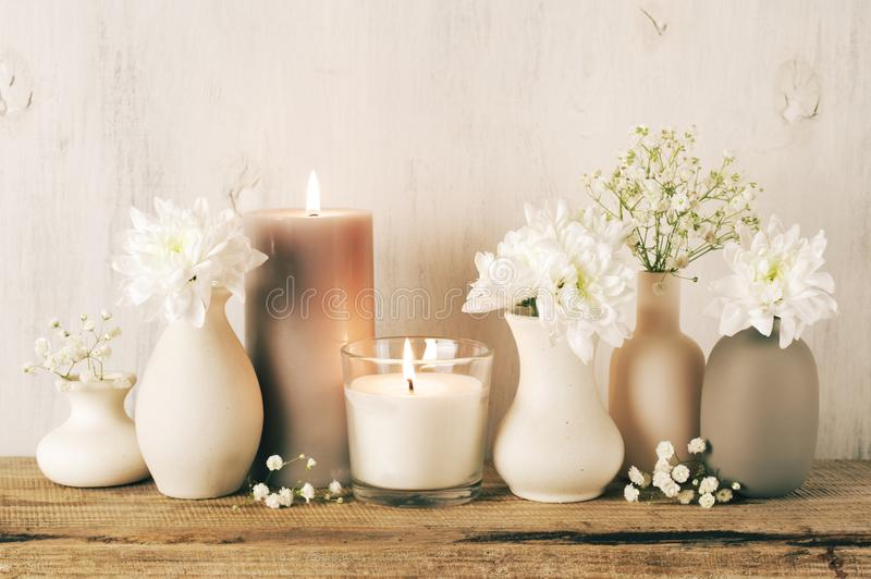 White flowers in neutral colored vases and candles stock images
