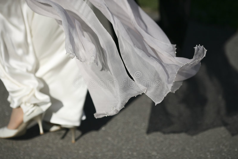 White flowing wedding dress. Married couple walking with flowing gown royalty free stock photography