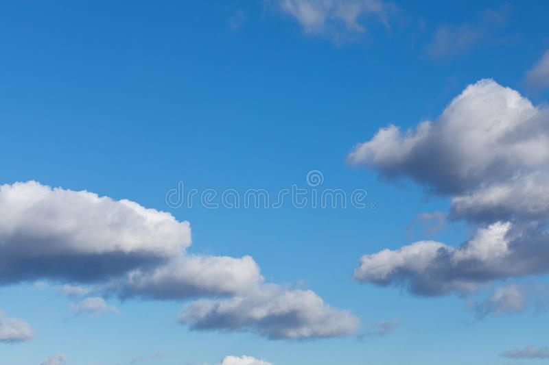 White, fluffy cloud float along the skyline over blue sky on a clear day. Background from clouds stock photography