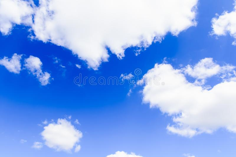 white fluffy clouds on a background of blue sky stock photography