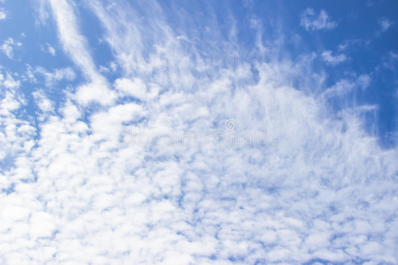 White fluffy clouds in the blue sky abstract background. stock photos