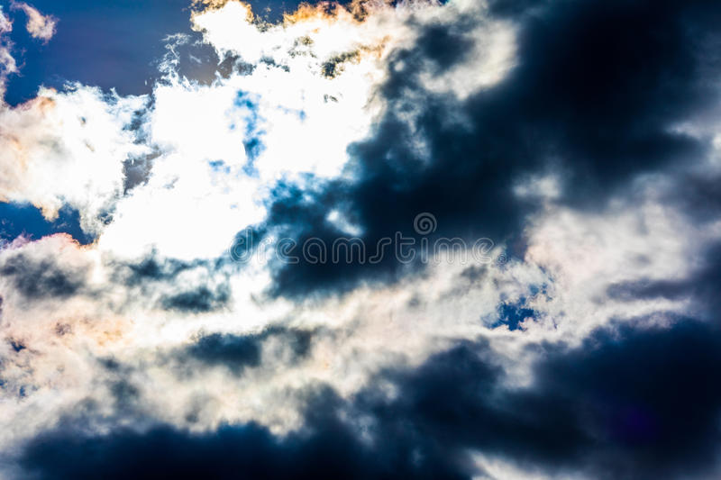 White fluffy clouds in the blue sky. Dramatic cloudscape with sun rays royalty free stock photo