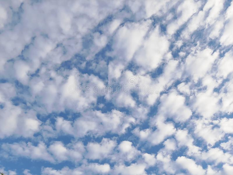 White fluffy clouds on blue sky. White fluffy clouds floating on blue sky on sunny day royalty free stock photo