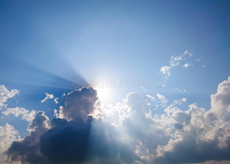 White fluffy clouds and sun reflect, in the blue sky. The cumulus occur in the bright morning. For background or display or backdrop stock images