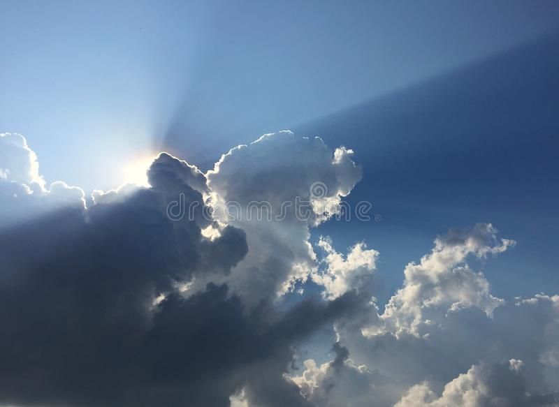 White fluffy clouds and sun reflect, in the blue sky. The cumulus occur in the bright morning. For background or display or backdrop royalty free stock photo
