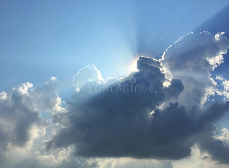 White fluffy clouds and sun reflect, in the blue sky. The cumulus occur in the bright morning. For background or display or backdrop stock photos