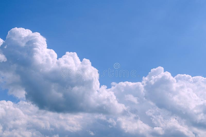 White fluffy clouds in the vast blue sky. Abstract nature background. Copy space for text. royalty free stock photography