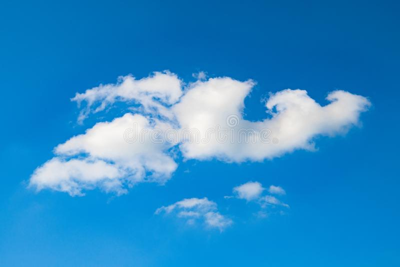 Fancy cloud in blue sky, fluffy, sweeping cloud in bright sky. White fluffy cumulus clouds blown by wind in clear blue sky stock images