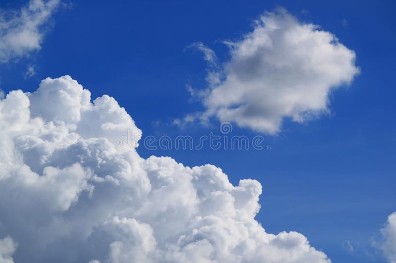White Fluffy Cumulus Clouds Floating on Vibrant Blue Sky royalty free stock image