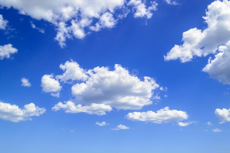 White fluffy cumulus clouds high in the blue summer sky. Cloud types and atmospheric phenomena. On a sunny day royalty free stock photos
