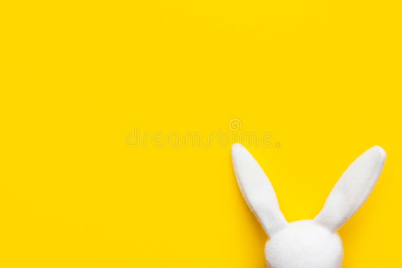 White fluffy fabric Easter bunny head on bright sunny yellow background. Blank face for drawing different expressions. Holiday card poster template with copy royalty free stock photos