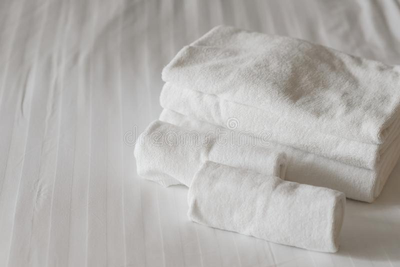 White fluffy towels on bed in hotel bedroom. royalty free stock photography