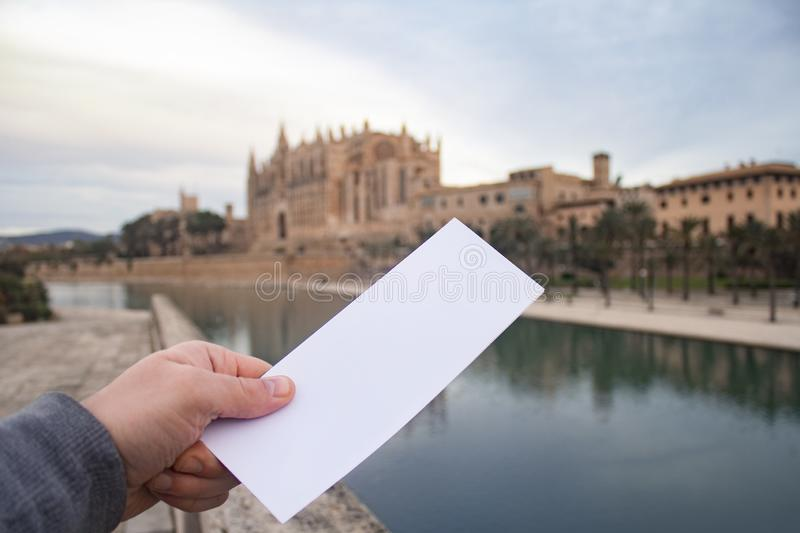 White flyer mockup in man`s hand on the background Catedral de Mallorca in Palma town on Mallorca Island in Spain.  stock image
