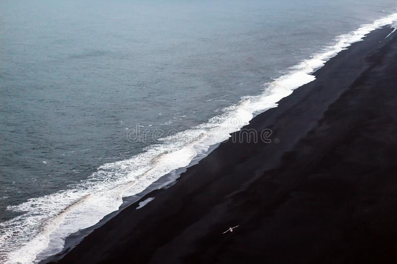 White foam on a black lava beach in southern Iceland. Sea aerial view and top view. Amazing nature, beautiful. Backgrounds and colors stock photography