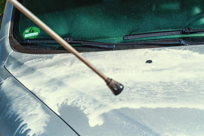White foam on cars bonnet applied by steam radiator. Cleaning silver cars bonnet at car wash by steam radiator with lots of foam stock photography