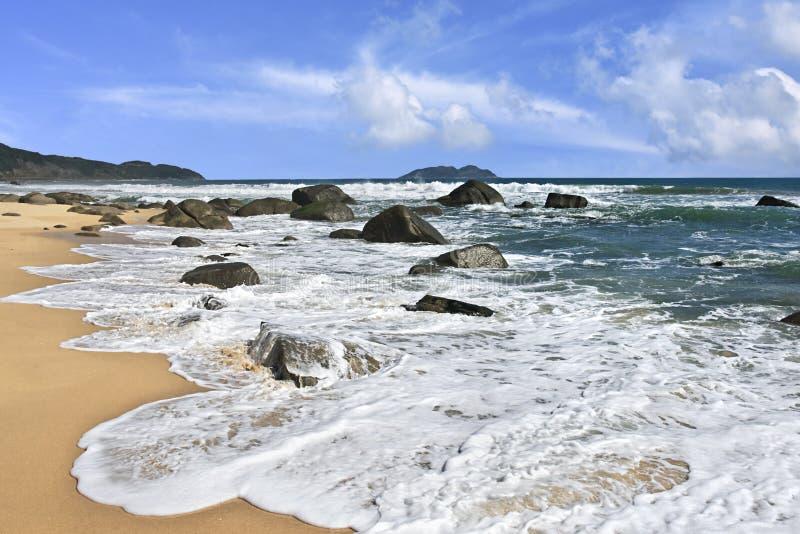 White foam of rolling waves in Sanya, Hainan Island, China. White foam of rolling waves in tropical Sanya, Hainan Island, China stock photo