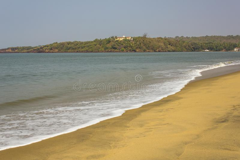White foam of waves at the yellow sandy beach against the blue sea and rocky beach with green trees and houses stock image