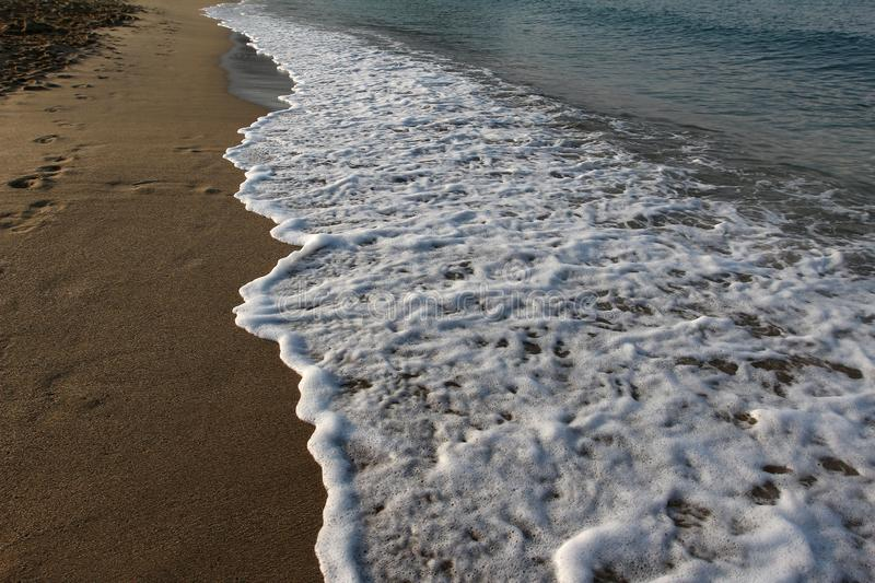 White foamy wave popping out on a beach stock image