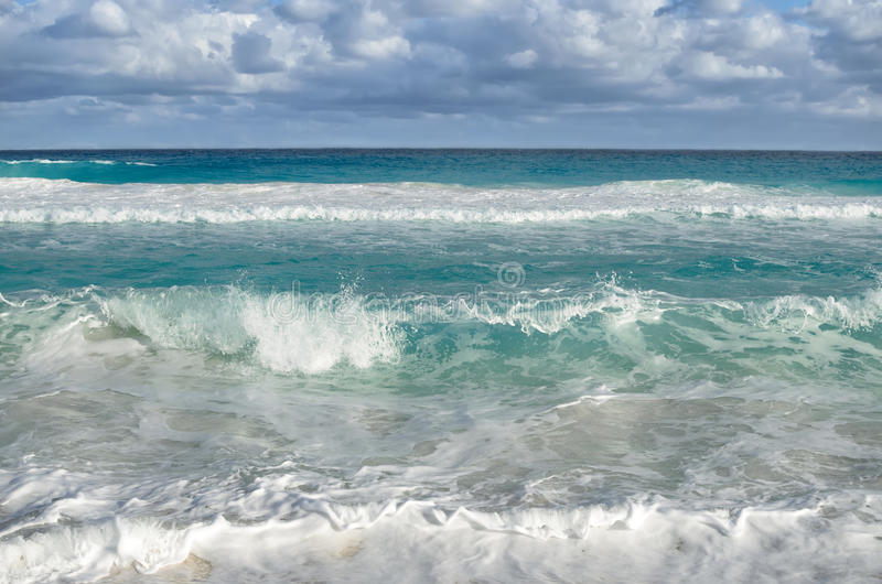 White foamy waves and gradually darkening color of sea water. With stripe of white sandy beach - perfect travel background royalty free stock image