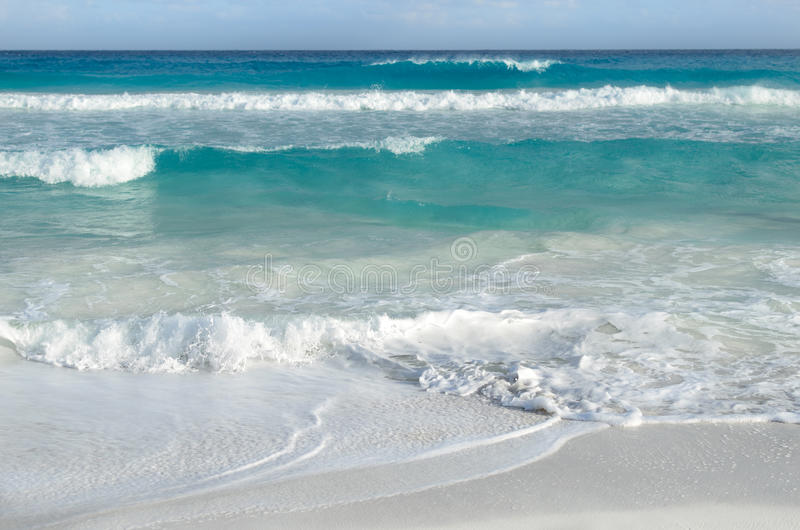 White foamy waves and gradually darkening color of sea water. With stripe of white sandy beach - perfect travel background royalty free stock photography