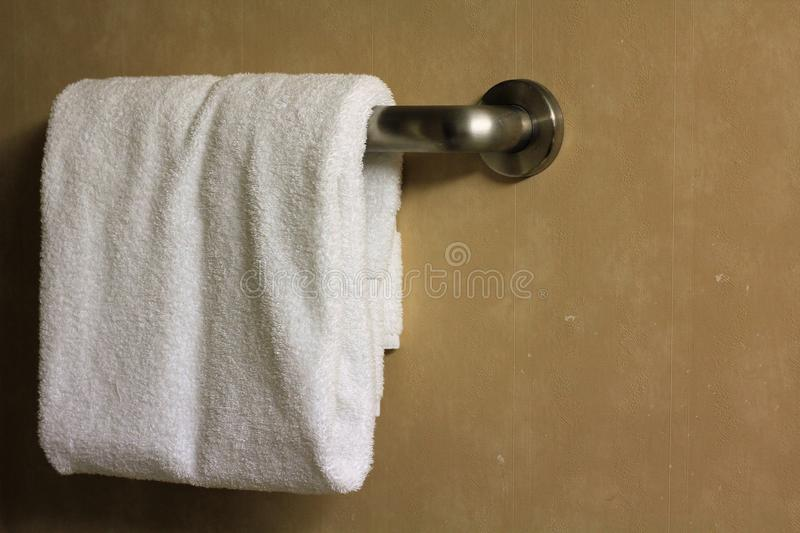 White folded bathroom towel on a rack. In a hotel bathroom stock photos