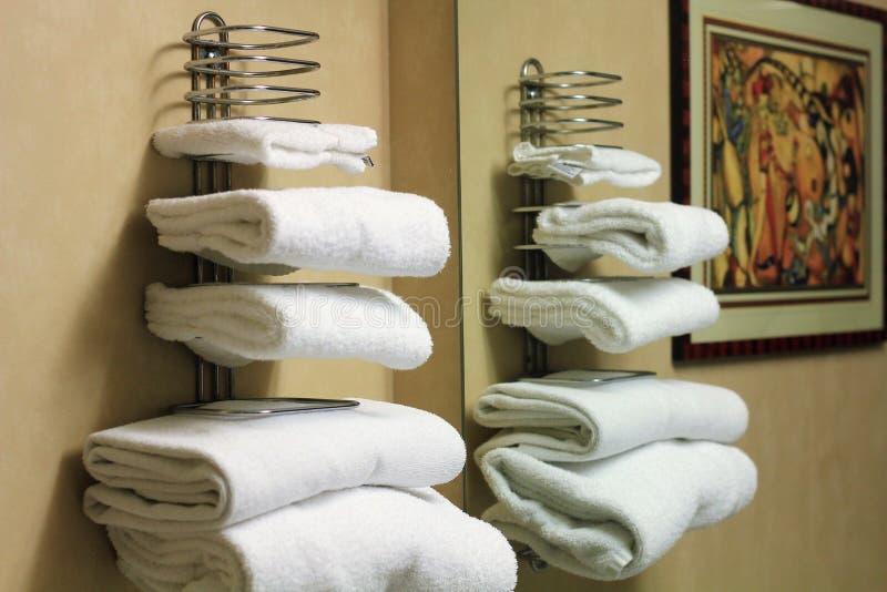 White folded bathroom towels on a rack. In a hotel bathroom stock photo