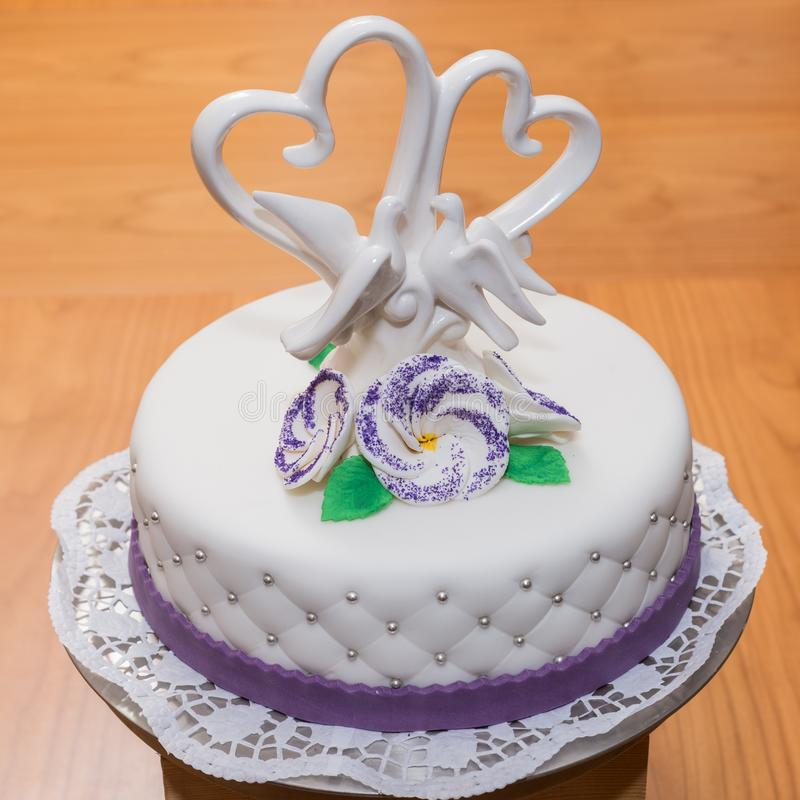 white fondant wedding cake with a heart and dove pigeon topper m stock images