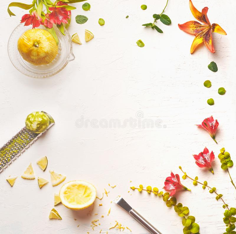 White food background with lemon juice, lime zest and flowers, top view royalty free stock photos