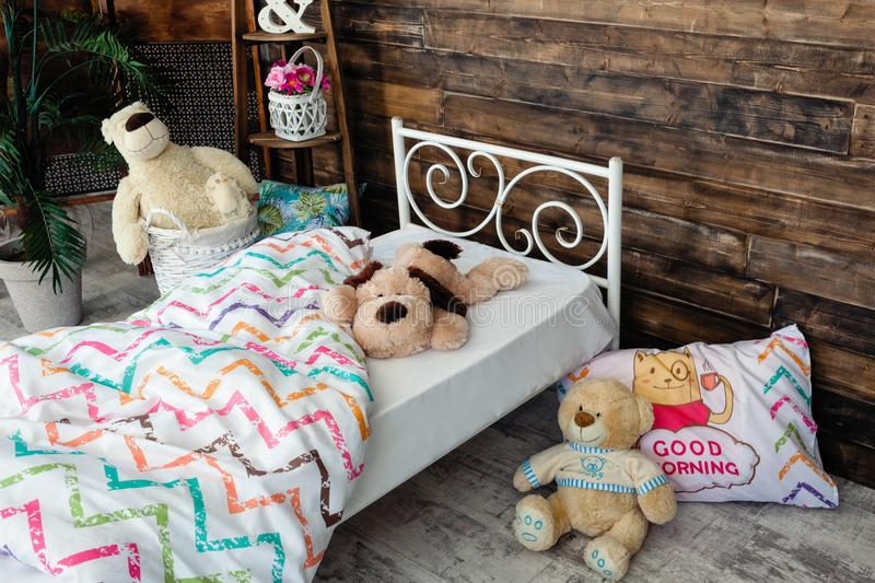 White forged crib. White bed forged wrought iron. Bed is covered with white linens. In the frame of soft toys stock image