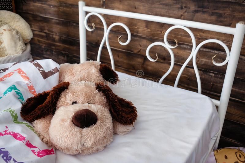 White forged crib. White bed forged wrought iron. Bed is covered with white linens. In the frame of soft toys stock photo