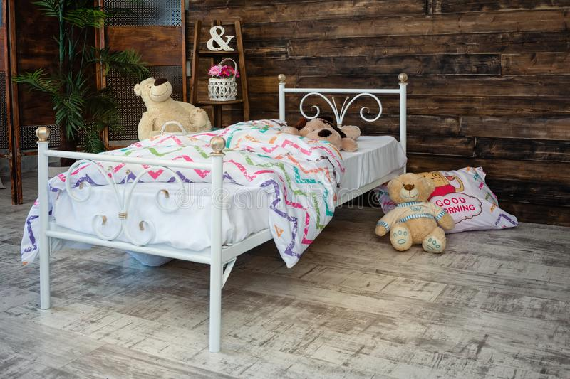 White forged crib. White bed forged wrought iron. Bed is covered with white linens. In the frame of soft toys royalty free stock image