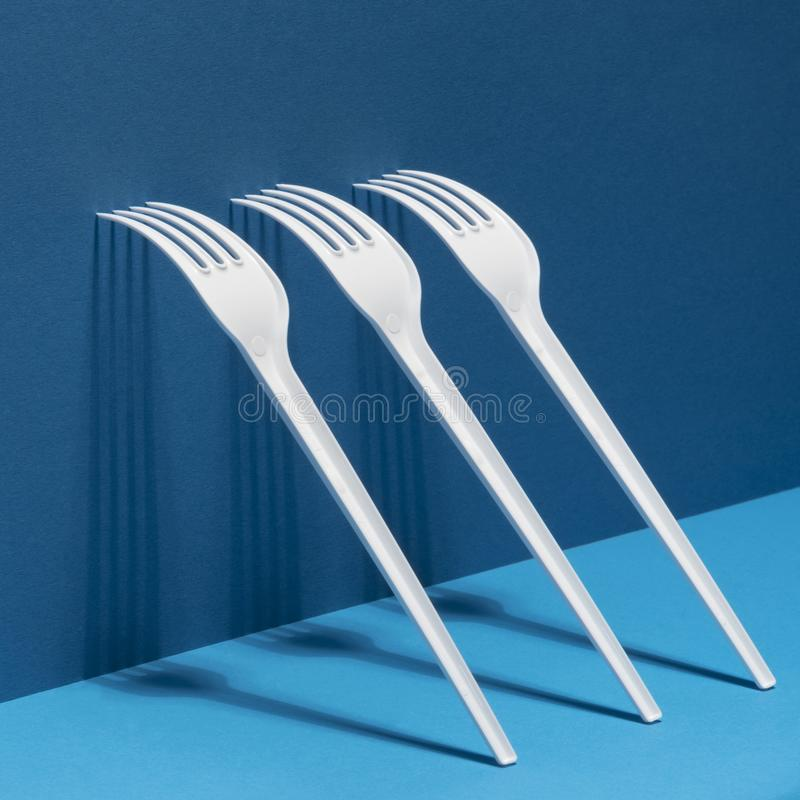 White forks with shadows on a mixed blue background. Modern conceptual art. stock photos