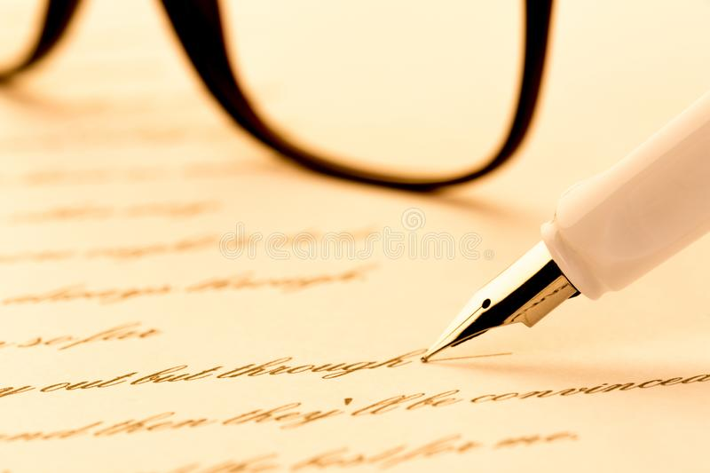White fountain pen writing a letter, glasses.  stock photos