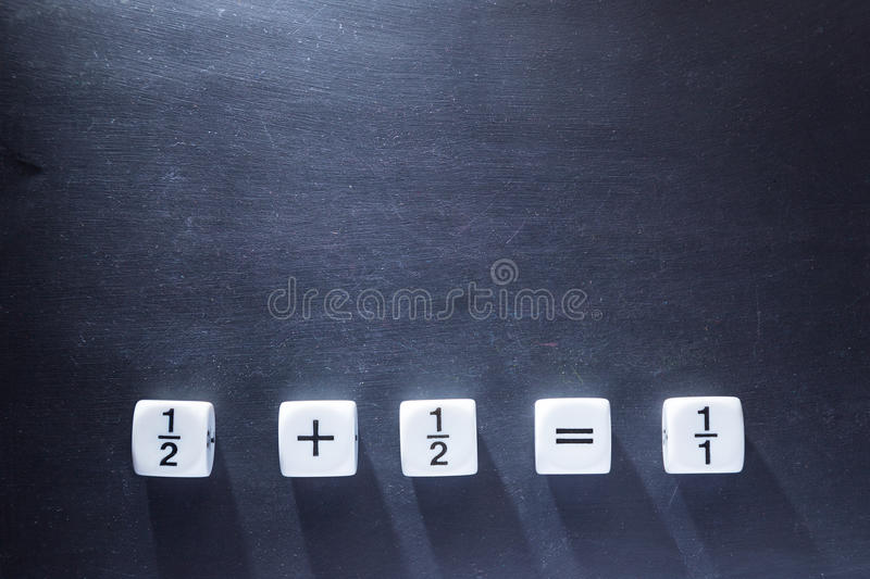 White fraction mah number dices showing simple equation on black. White fraction mah number dices showing simple equation, half plus half equal whole, on stock photos