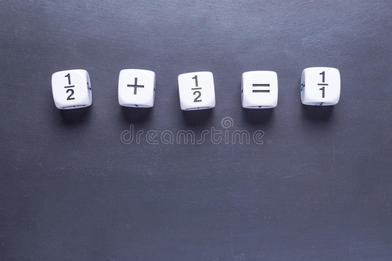 White fraction mah number dices showing simple equation on black. White fraction mah number dices showing simple equation, half plus half equal whole, on stock images