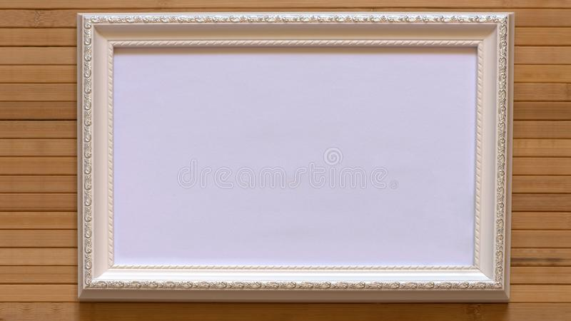 White frame with empty white canvas on natural bamboo wall. stock image