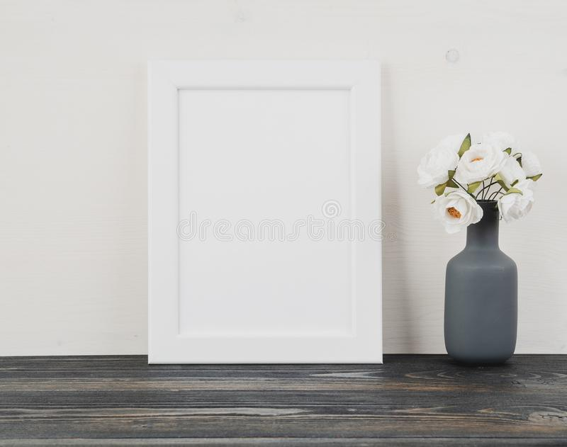 White frame, flower in vase, clock on dark grey wooden table against the white wall with copy space. Mock up. royalty free stock images
