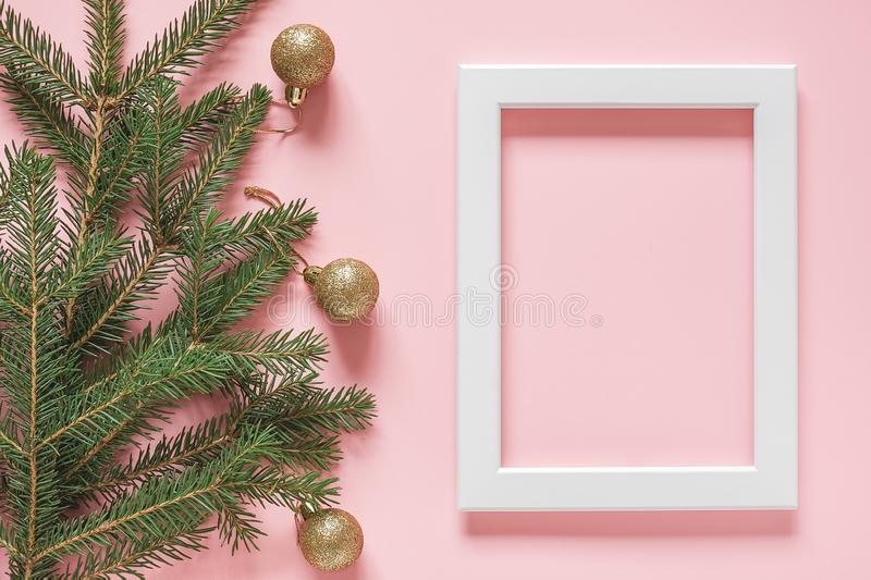 White frame and green spruce branch with gold christmas balls on pink background. Concept Merry christmas or Happy new year. Top royalty free stock images