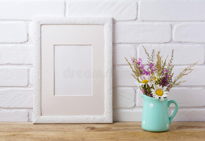White frame mockup with chamomile and purple field flowers in mi stock photography