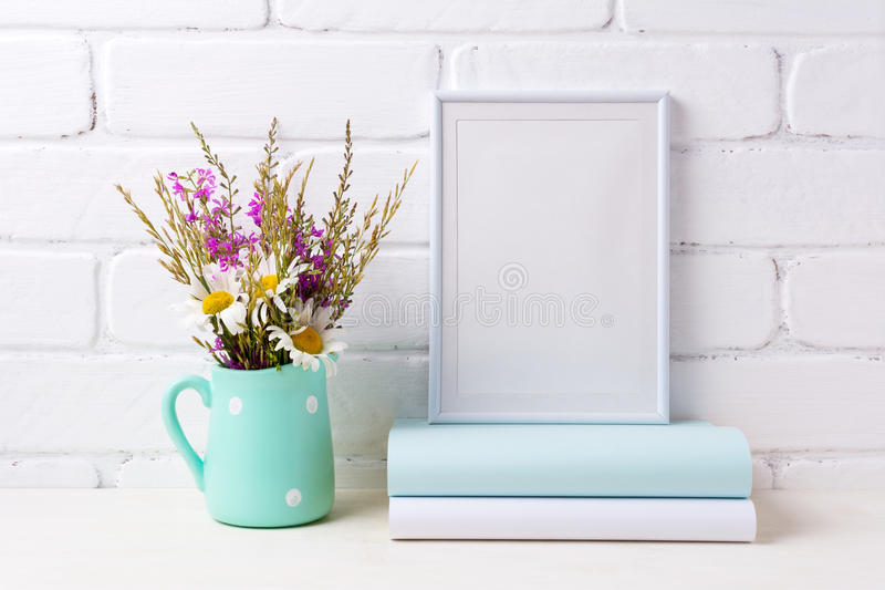 White frame mockup with chamomile and purple flowers in mint green pitcher and books royalty free stock photos