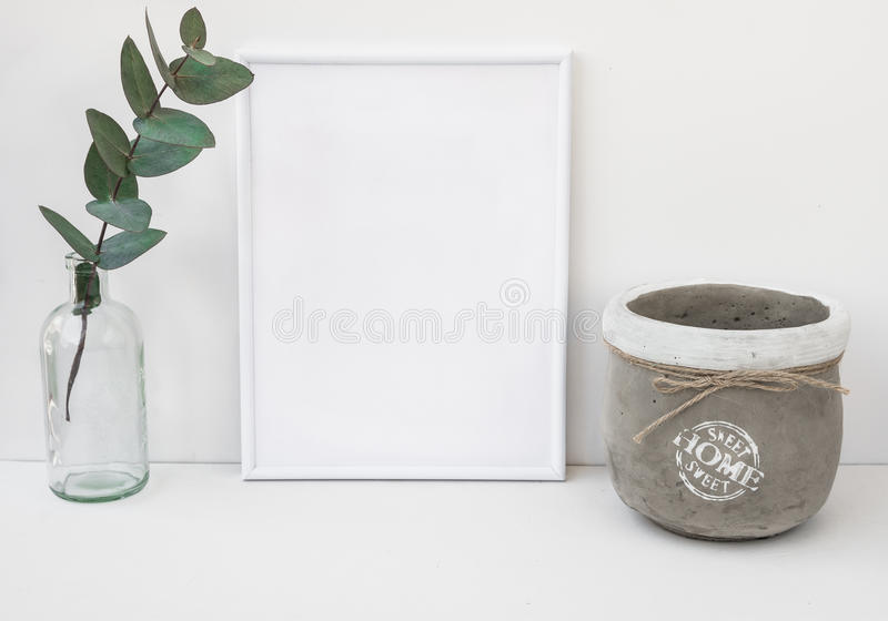 White frame mockup, eucalyptus branch in glass bottle, cement bowl, styled minimalist clean image for product marketing royalty free stock photo